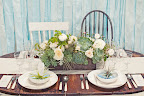 The table was anchored by an arrangement of pale blooms and succulents.