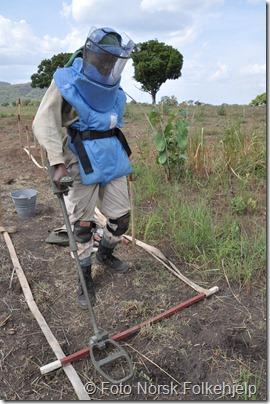 Diana Likiso James fra det kvinnelige mineryddeteamet har akkurat funnet en TM46 (Russisk anti-tankmine) utenfor Lainya.<br /><br />Bakgrunn:<br />Et av flere kvinnelige minerydderteam som driver manuell minerydding. <br />Team består av 27 mineryddere, en sykepleier, en sjåfør, en kokk, to vakter, leder Senya Jane (ikke avbildet) og nestleder .<br />Bildene er fra task 782 B like nord for byen Lainya langs hovedveien mellom Yei og Juba.<br />Området de rydder vil bli brukt til gjenbosetting av flyktninger etter krigen og til jordbruksland. Sannynsligvis vil dagens bysenter, som grenser helt opp til minefeltet, flyttes til dette området så snart det er ryddet og frigitt.<br />Siden minefeltet ligger helt inntil hovedveien må veien stenges når det pågår rydding. Veien holdes stengt i 45 min og åpent i 15 min hver time. Dette gir også minerydderne en etterlengtet pause i arbeidet.<br />Dette området ryddes av ett kvinnelig, to mannlige og et teknisk team som benytter Mine Wolf Tiller og Flale (minefres).