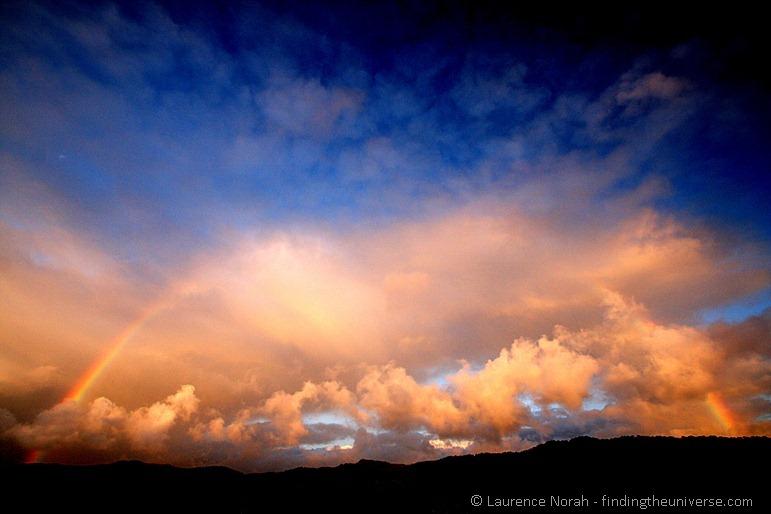 Sonnenuntergang mit Regenbogen über den südlichen Alpen