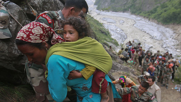 Indian soldiers help a woman carrying a child on her back during rescue operations in Govindghat in the Himalayan state of Uttarakhand, after flash floods and landslides unleashed by early monsoon rains, 23 June 2013. Photo: Danish Siddiqui / REUTERS