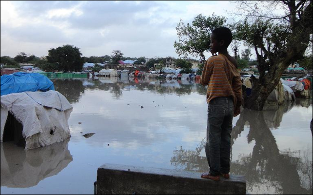 A Somalian internally displaced child looks at a flooded section of a camp in Mogadishu on 4 August 2012, following heavy rain and flash floods. Photo: Abdurashid Abdulle / AFP