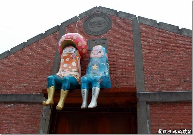 高雄-駁二。真羨慕這兩個小朋友就這樣坐在台糖舊倉庫的大門上面!什麼也不用作,悠閒地坐在高處看過往遊客,不過也不是那麼好就是了,因為不能到處晃啊!還要成風吹與淋。這兩個小朋友,一個有著鮮艷點點帶了一頂類似草菇造型帽子,另一個應該是外太空牛仔吧!因為身上有著星星及「COW」字樣,還有像極火箭造型的大頭。