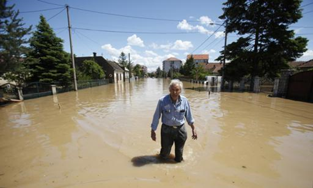 A man walks through flood water in the town of Obrenovac, 18 May 2014. Soldiers, police and villagers battled to protect power plants in Serbia from rising flood waters on Sunday as the death toll from the Balkan region's worst rainfall in more than a century reached 37. Twelve bodies were recovered from the worst-hit Serbian town of Obrenovac, but the number was likely to rise as waters receded. Photo: Antonio Bronic / REUTERS