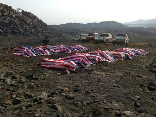 This photo that appeared anonymously on Facebook on Thursday, 4 July 2013, shows what officials confirmed to The Associated Press, as the 19 dead firefighters draped in American flags by Yavapai County Sheriff Scott Mascher, shortly after they were found dead near Prescott, Ariz., on 30 June 2013. Several media outlets, including the Arizona Republic and USA Today, published the photo on Friday, 5 July 2013. Nineteen members of the Granite Mountain Hotshot crew died Sunday, 30 June 2013 fighting the Yarnell Hills Fire, about 40 miles southwest of Prescott. Photo: AP