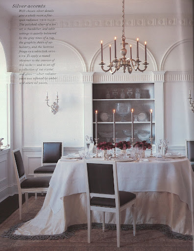 The polished silver of a tea set, a chandelier, and table settings is quietly bolstered by the gray tones of a rug, the graphite sheen of upholstery, and the lustrous fringe on a tablecloth.
