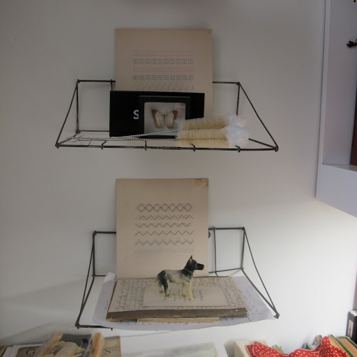 Vintage wire shelves display some of Fritz's favorite objects, including figurines and sewing patterns.