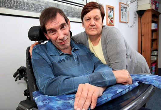 "Jane Nicklinson with husband Tony Nicklinson at home in Melksham, Wilts. A father-of-two with ""locked in"" syndrome says he will go to Swiss clinic Dignitas to die - unless the British Government changes the law on assisted suicide. Civil engineer Tony Nicklinson, 56, lost all movement in his body from the neck down after suffering a sudden catastrophic stroke on a business trip to Greece in 2005. The helpless husband is confined to a wheelchair and can tragically only communicate through moving his head and eyes. Now he says he wants wife Jane, 55, to help him in a ""mercy killing"" - or the determined dad will fly out to the assisted dying group Dignitas in Switzerland. See swns story SWLOCK , 17 Dec 2010."