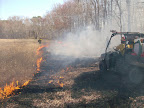 Polaris Ranger crew moving up to extinguish line between pond and the woods