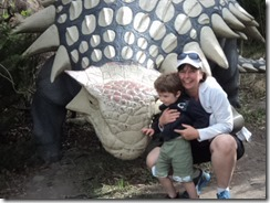 posing with a dino at the zoo