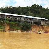 写真6  崩落の危機にあるロングハウス/ Photo6 A longhouse on the verge of collapse due to river erosion