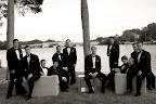 Mark and the groomsmen, out by the water, pose for a portrait (with photographer Missy McLamb). The furniture vignette offered a great setting for the group photo.
