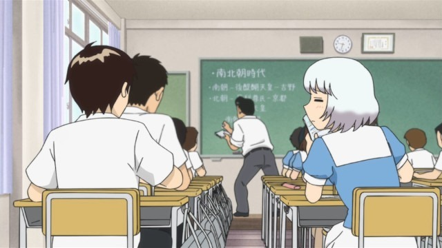 View from behind the two as Rumi leans over to chastise Seki in the middle of class