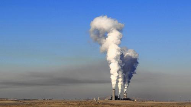 A layer of haze looms west of the Four Corners Generating Station in New Mexico. Southern California Edison recently sold its stake in the power plant, but the facility still burns coal to produce power that goes to Arizona customers instead. Photo: Josh Stephenson / Durango Herald
