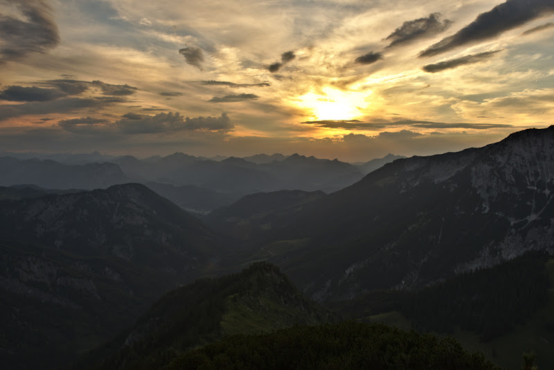 Fiery sunset partially hidden by the incoming weather front, near Stripsjochenhaus, Wilder Kaiser in Austria.