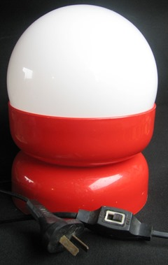Lamp with red plastic base and glass dome
