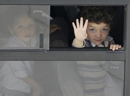 Un bambino su un autobus mentre aspetta di essere imbarcato verso la Sicilia.