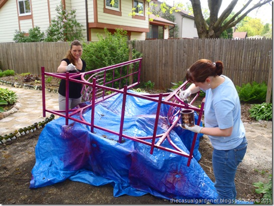 Shawna and Katie top coat painting the wrought iron arbor.