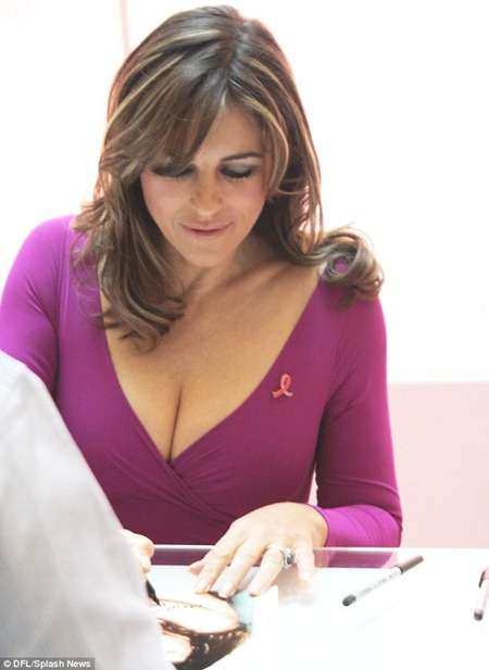 Liz Hurley writing a message at Breast Cancer Awareness campaign