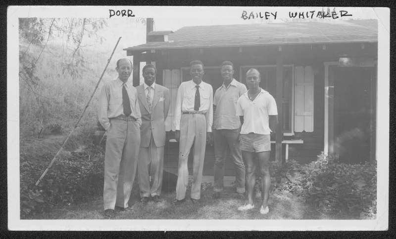 W. Dorr Legg (left) stands next to partner Bailey Whitaker and others outside a home. Undated.
