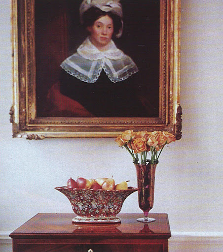 A wooden side table sits beneath an unsigned portrait that has been attributed to the artist Samuel F.B. Morse, who was also the inventor of the Morse code.