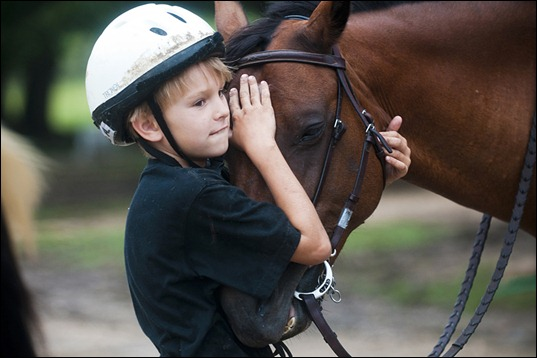 07/01/10 Jarrad Henderson/ AMERICAN-STATESMAN<br />Triston Anderson,8, hugs his horse after a trail ride at Hunters Chase Farms on July 1, 2010. Like Anderson, many of the kids at this camp have never been on a farm before. The overnight camp learning process allows kids to feel more comfortable and safe around farm animals like horses. The opportunities at Hunters Chase Farms are immense. Visitors can learn how to ride a horse, learn how to jump a horse, or come to rodeos on the property.