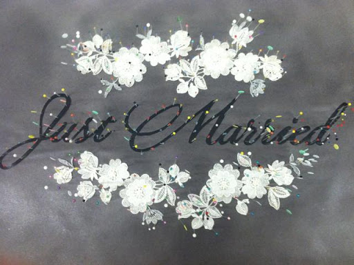Lace applique and lettering pinned on paper
