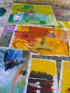 Completed paintings are laid on the floor of Booth's studio.