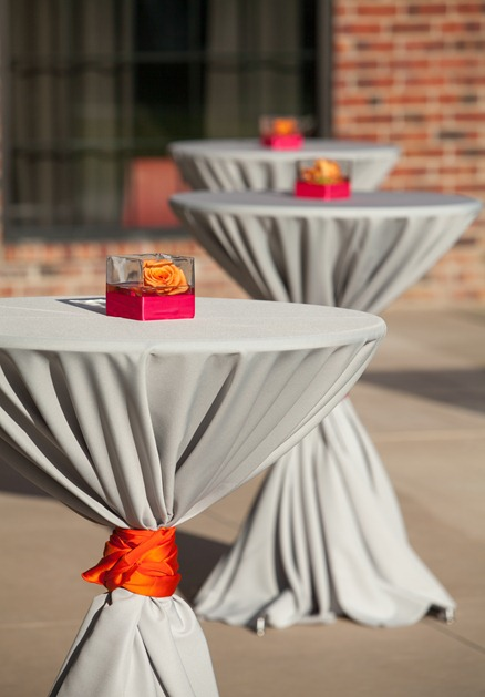 outdoor cocktail tables were covered in a gray tablecloth and tied ...