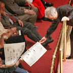 Louis Langree passes out pages of the score to Krzysztof Penderecki's