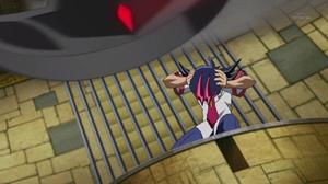 Yuma se abaixando da lâmina que do nada apareceu acima de sua cabeça.