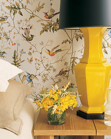 A yellow lamp with a black shade adds a bold element, while ecru and cream bedding, a blond-wood side table, and a jute rug temper the intensity of the walls, creating a balance of elements that's romantic but not predictable and feminine.