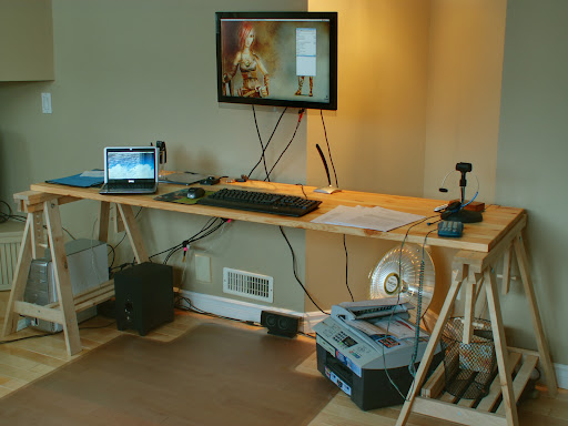 Full adjustable workspace: the table can be raised 70 cm higher (so I can work either standing or sitting), and the monitor is attached on a flexible wall-mounted arm that can tilt, rotate and swivel in pretty much all directions (only its height cannot be adjusted). HDR picture taken with a Konica Minolta DiMage Z5 and processed with Enfuse (part of Hugin). Running Ubuntu as the O.S. The character on my wallpaper is Sintel, from http://durian.blender.org