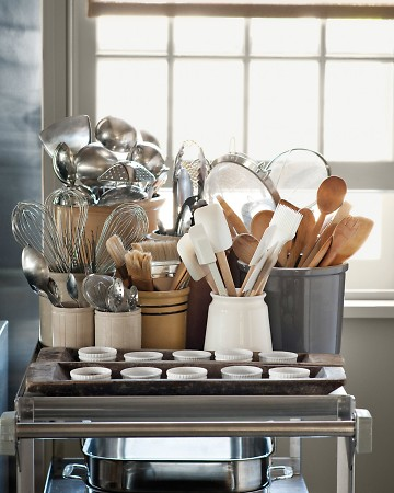 Martha keeps ladles, whisks, pastry brushes, wooden spoons, and flexible spatulas in separate containers on a cart, which is well within reach of where she is cooking.