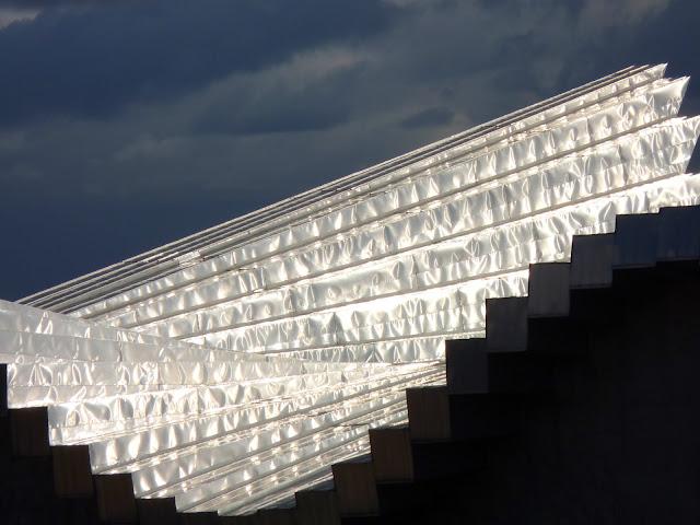 la fachada principal sur es ciega salvo en su cuerpo central donde se sita el centro de visitantes que presenta un singular mirador de madera tanto