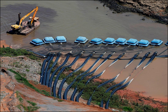 Machines providing water and sewage services to residential, commercial, and industrial areas work next to pumps from the Brazil's depleted Jaguari dam. Photo: Paulo Whitaker / Reuters