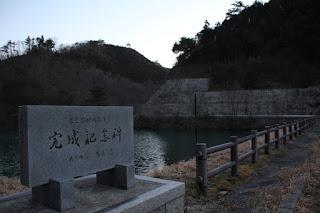 天端より完成記念碑とダム湖を望む