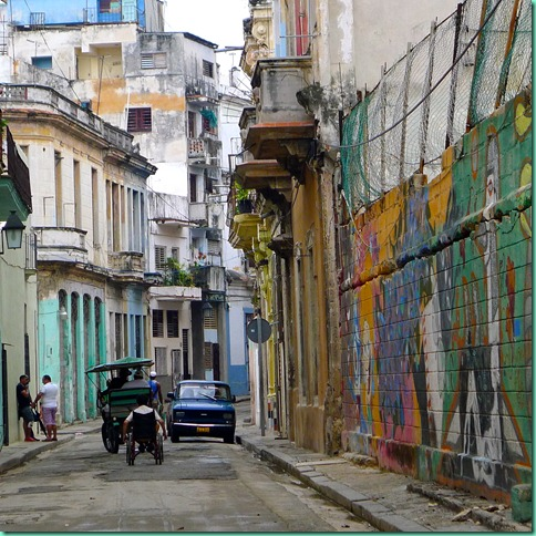 Havana scenery, narrow street, balconies, wheelchair, painted wall