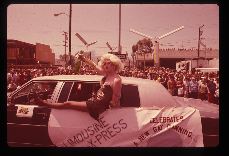 Drag queen posing with a beverage in a limousine at the Los Angeles Christopher Street West pride parade. 1982.