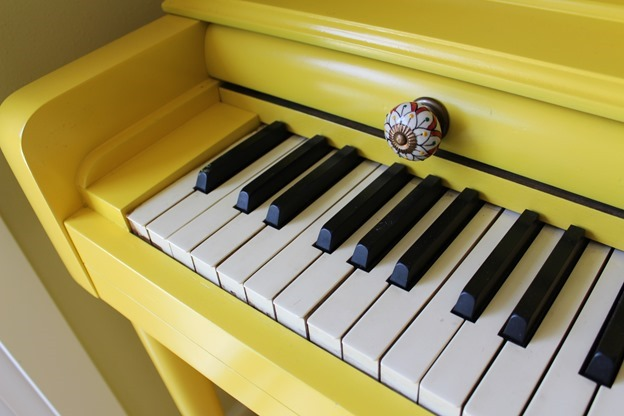Painted yellow piano with Anthropologie knobs