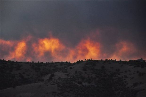 This photo provided by the American Red Cross, flames from the Doce Fire rise above a hillside in Arizona's Prescott National Forest at dusk, 18 June 2013. More than 500 firefighters were dispatched to battle the nearly 11-square-mile wildfire which sparked evacuations in nearby neighborhoods. Photo: Associated Press