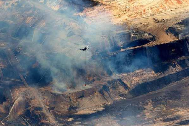 A water-bombing helicopter flies over the burning coal mine near Morwell, Australia, on 23 February 2014. Photo: Jason South / The Age