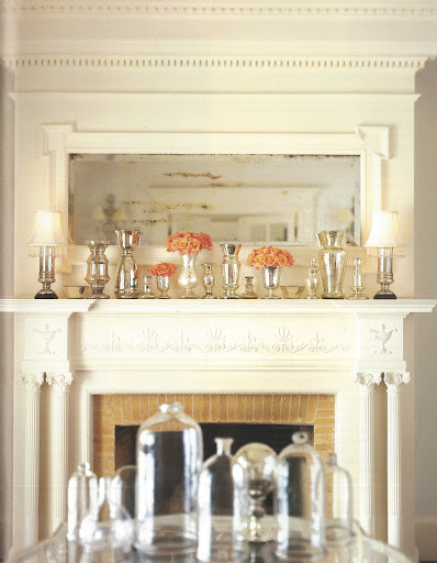On the shelf of a mirrored mantelpiece, reflective mercury-glass lamps, vases, and other vessels provide a warm, luminous setting for the roses that bring the only touch of intense color.