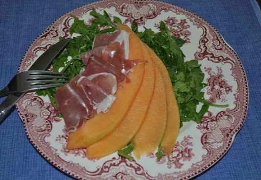 Cantaloupe and prosciutto over arugula