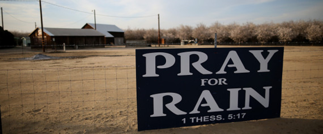 A sign on a California farmhouse fence reads, 'Pray for rain - 1 Thess. 5:17'. Photo: Justin Sullivan / Getty Images