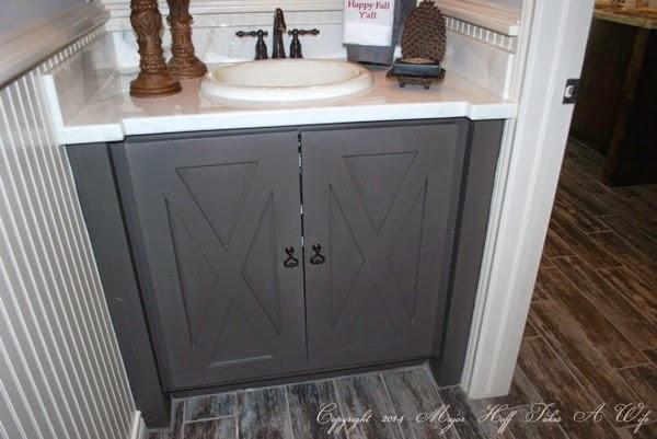 Barn door style cabinet doors in dark gray paint with beadboard wall