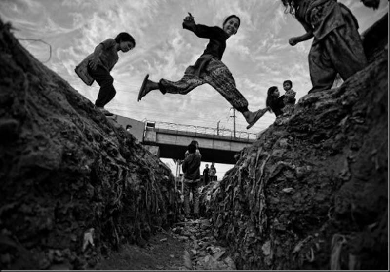 Lo slum si sviluppa ai margini di una discarica che i bambini utilizzano come parco gioch