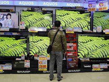Homem olha para televisores da Sharp à venda em uma loja de eletrônicos em Tóquio: economia cresceu a uma taxa anualizada de 4,1% no primeiro trimestre