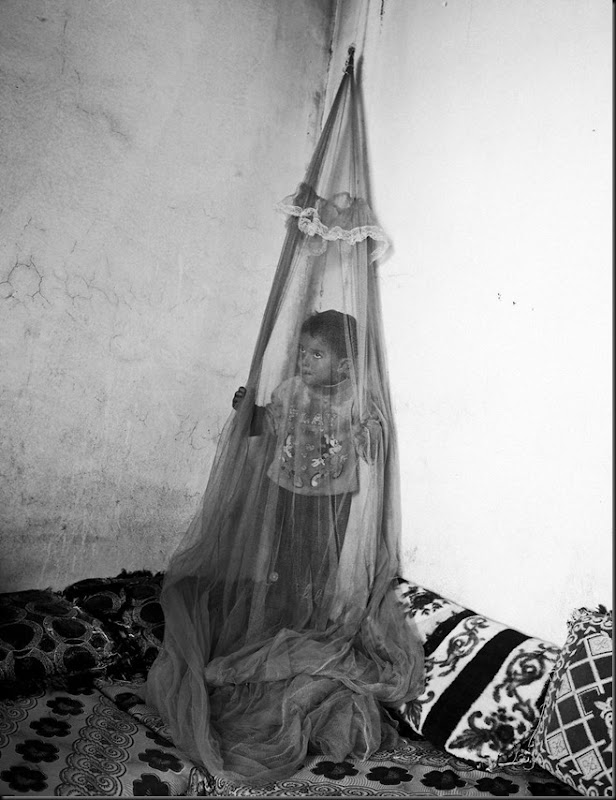 Khoder, 10, stands behind a mosquito net inside a temporary house in the Bekaa Valley, Lebanon. (Moises Saman/Magnum Photos for Save the Children)