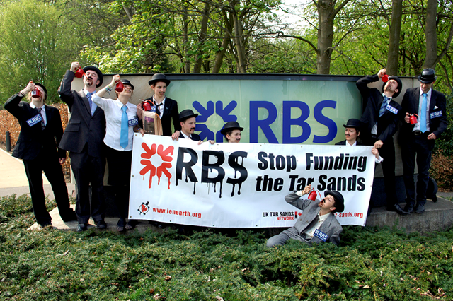 Environmental campaigners dressed as bankers protest outside the RBS Headquarters at Gogarburn in Edinburgh ahead of the bank's AGM, 19 April 2011. Human rights and environmental campaigners dressed as oil-addicted bankers drinking from oil cans, demanded an end to the bank's support for the fossil fuel industry. They were joined by several Canadian First Nations representatives who arrived to personally urge for RBS to cease financing tar sands companies extracting oil on their lands. Photo: Richard Scott / MAVERICK