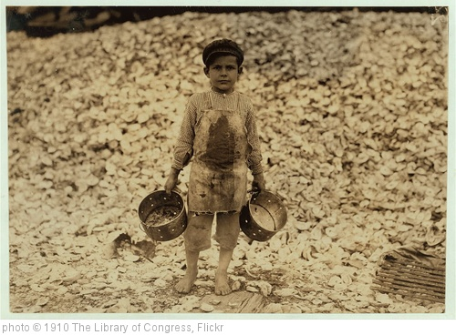 'Manuel, the young shrimp-picker, five years old, and a mountain of child-labor oyster shells behind him. He worked last year. Understands not a word of English. Dunbar, Lopez, Dukate Company. Location: Biloxi, Mississippi. (LOC)' photo (c) 1910, The Library of Congress - license: http://www.flickr.com/commons/usage/